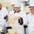 Stock Photo: Teacher showing her students how to mix dough