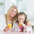 Woman and Child sitting at the kitchen table holding a glass of — Stock Photo