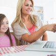 Mother pointing something out on laptop for daughter — Stock Photo