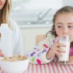 Постер, плакат: Little girl drinking milk