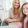 Womtyping at laptop with daughter — Stock Photo #23106454