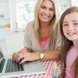 Woman typing at the laptop with daughter — Stock Photo