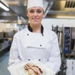 Smiling chef showing her plate — Stock Photo