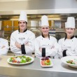 Stockfoto: Smiling Chef's standing behind salads