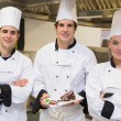 Foto de Stock  : Three Chef's presenting cake