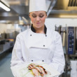 Smiling chef looking at her plate — Stock Photo #23107112