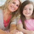 Mother and child sitting at kitchen table smiling — Stock Photo #23107894