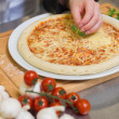 Pizza being garnished with basil leaf — Stock Photo