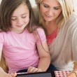 Child using tablet pc with mother in kitchen — Stock Photo