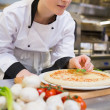 Stockfoto: Chef putting basil leaf on pizza