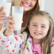 Mother and daughter raising milk glasses — Foto de Stock