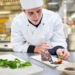 Cheerful chef putting mint with his dessert  — Stockfoto