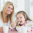 Little girl eating cereal at breakfast with her mother — Stock Photo #23108808