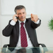 Businessman phoning and pointing — Stock Photo #23108828