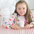 Happy little girl with glass of milk getting cereal from her mot — Stock Photo #23108898
