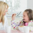 Girl feeding her mum cereal — Stock Photo #23108934