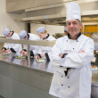 Head chef smiling with his team working behind him — Stock Photo