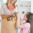 Woman giving green pepper to daughter from grocery bag — Stock Photo #23108994