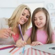 Foto Stock: Mother and daughter drawing together
