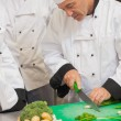 Chef teaching group how to slice vegetables — Stock Photo #23109416