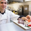 Stock Photo: Smiling chef garnishing slice of cake