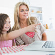 Child pointing something out on laptop to mother — Stock Photo