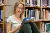 Mujer sentada en la biblioteca en el piso — Foto de Stock