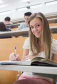 Woman sitting at the lecture hall making notes — Stock Photo