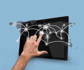 Finger selecting world map on tablet pc — Stock Photo