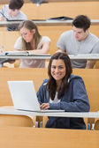 Smiling student in lecture with laptop — Foto Stock
