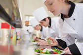 Chef finishing her salad in culinary class — Stock Photo