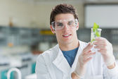 Student standing at the laboratory holding beaker with seedling — Stock Photo