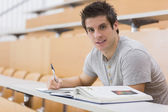 Student sitting at the desk smiling — Stock Photo