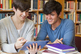 Students sitting at library desk looking at tablet pc — Stock Photo