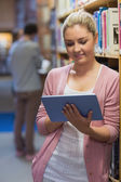 Woman using tablet pc in college library — Stock Photo