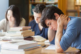 Student falling asleep in library — Stock Photo