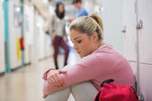 Student sitting on the floor at the hallway looking disappointed — Stock Photo