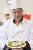 Smiling chef showing his salad — Stock Photo
