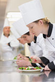 Chef's applying finishing touches to salads — Stock Photo