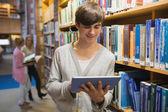 Estudiante que esté usando el tablet pc de pie en la biblioteca — Foto de Stock