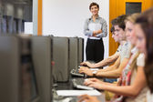 Teacher standing while students sitting at the computer — Stock Photo