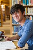 φοιτητής κάθεται στη βιβλιοθήκη — Φωτογραφία Αρχείου