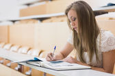 Concentrating woman sitting at the lecture hall writing — Stock Photo