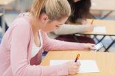 女孩在考试期间检查电话 — 图库照片