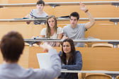 Students sitting at the lecture hall with man razing hand to ask — Stock Photo