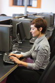 Concentrate woman sitting at the computer typing — Stock Photo