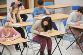 Students writing in the exam hall — 图库照片