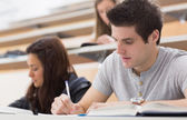 Students sitting at the lecture hall while writing — Stock Photo