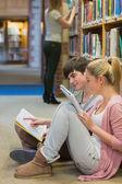 Studenti seduti sul pavimento della biblioteca e lo studio — Foto Stock