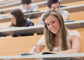 Woman sitting at the lecture hall while smiling — Stock Photo
